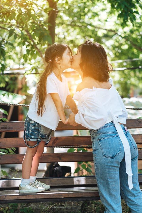 Madre joven que abraza a su niña en el parque imagen de archivo libre de regalías