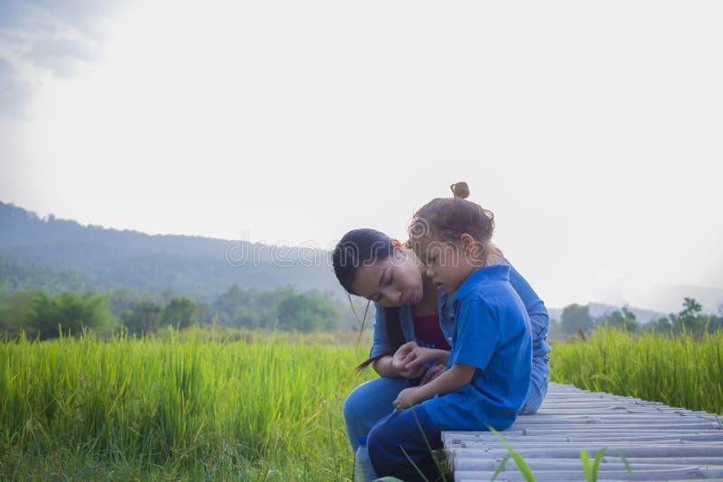 Madre joven que abraza y que calma un peque?o muchacho largo gritador del pelo, a una madre asi?tica intentando confortar y calma imágenes de archivo libres de regalías