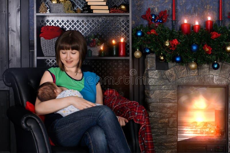 Madre joven que amamanta y que mira con amor su bebé cerca de la chimenea La pared detrás se adorna con las bolas de la Navidad imagen de archivo