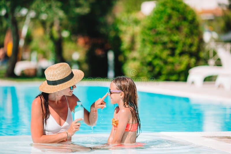 Madre joven que aplica la crema del sol a la nariz de la hija foto de archivo libre de regalías