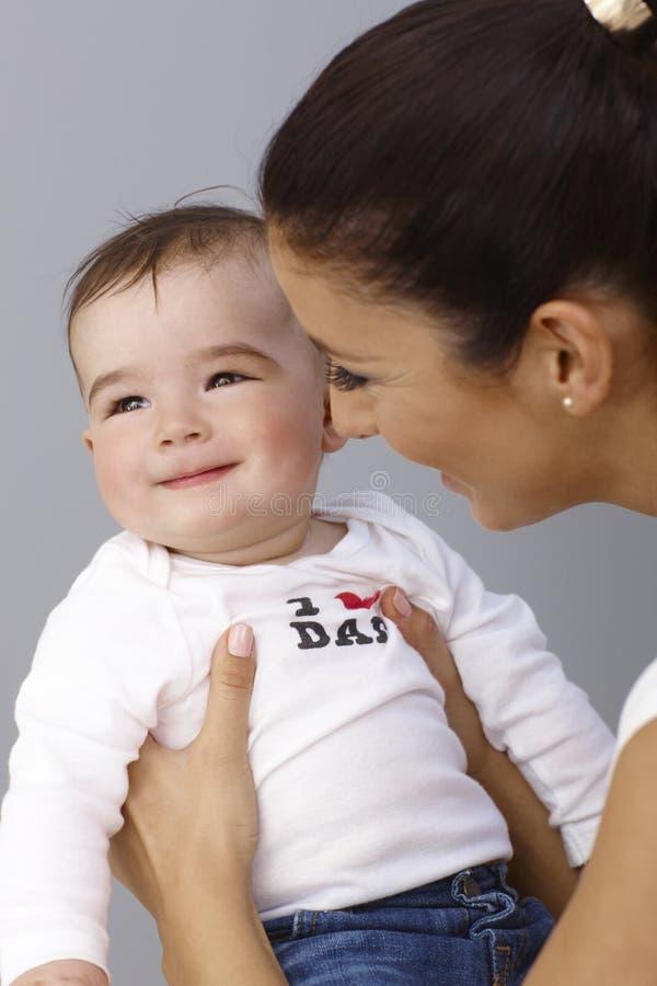 Madre joven que besa al bebé hermoso foto de archivo