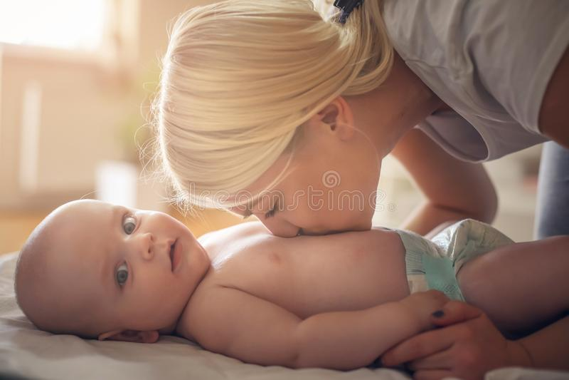 Madre joven que besa a su pequeño bebé en pañales Cierre para arriba foto de archivo libre de regalías