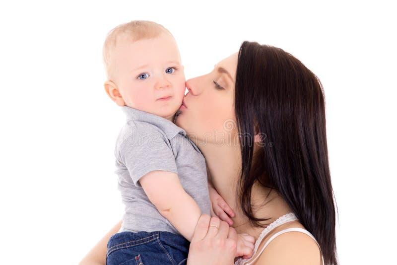 Madre joven que besa a su pequeño hijo aislado en blanco fotografía de archivo