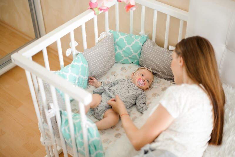 Madre joven que calma al pequeño bebé recién nacido lindo en cama imágenes de archivo libres de regalías