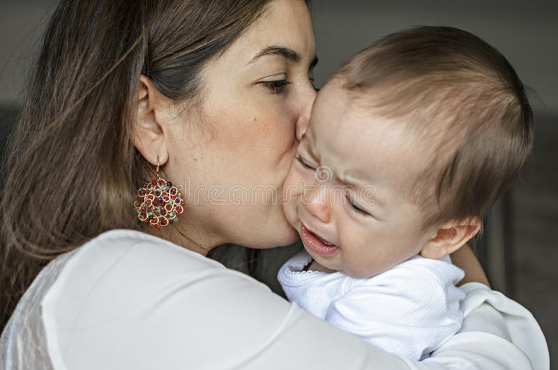Madre joven que calma a un bebé gritador imagen de archivo