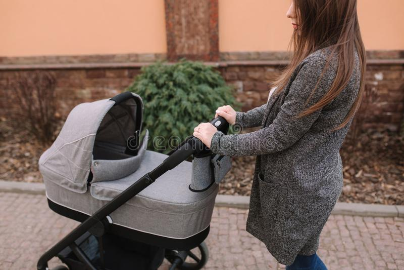 Madre joven que camina con su bebé recién nacido en cochecito Cochecito de niño gris Mamá hermosa en gafas de sol imagenes de archivo