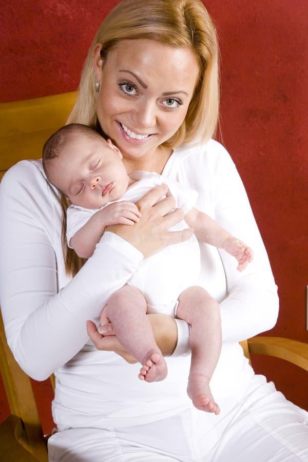 Madre joven que celebra al bebé recién nacido en brazos imagen de archivo