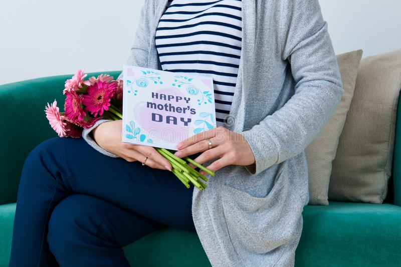 Madre joven que celebra el ramo de margaritas del gerbera y de tarjeta de felicitación del día del ` s de la madre que se sientan imágenes de archivo libres de regalías