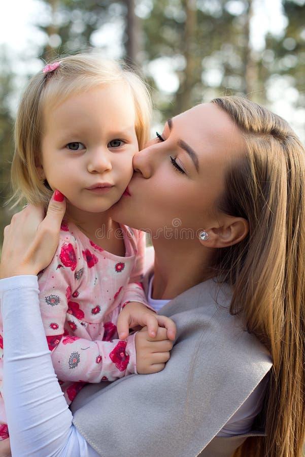 Madre joven que celebra a la hija linda de la niña pequeña en sus brazos y que le da un beso en una mejilla imágenes de archivo libres de regalías