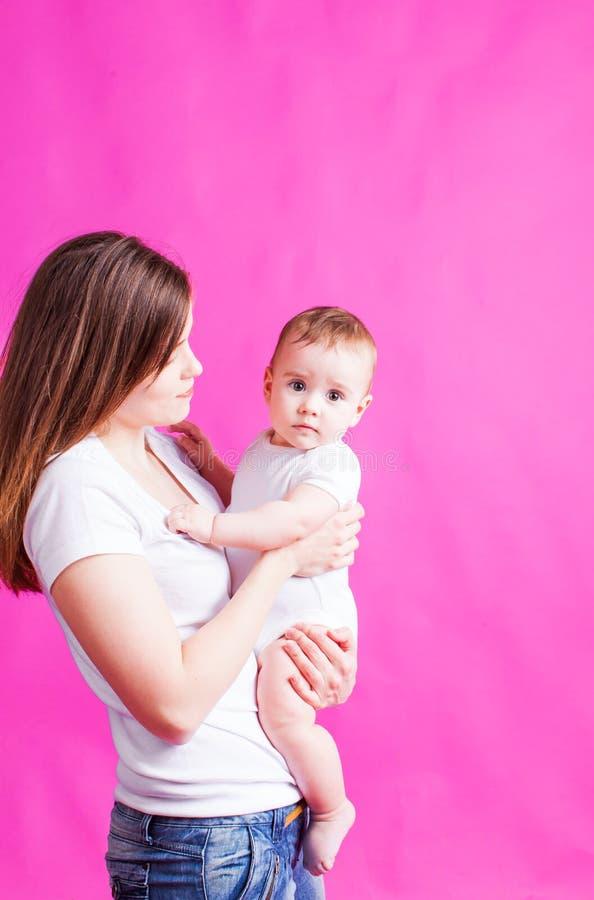 Madre joven que celebra a su bebé, en un fondo rosado fotos de archivo libres de regalías