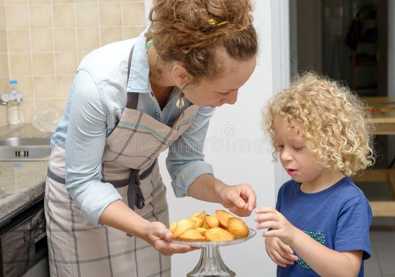 Madre joven que da las galletas a su niño imagen de archivo libre de regalías