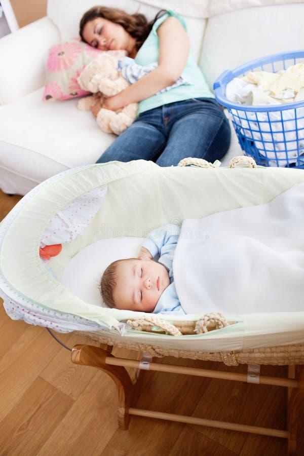 Madre joven que duerme en el sofá con su bebé imagen de archivo