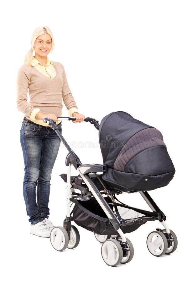 Madre joven que empuja un cochecito de bebé foto de archivo libre de regalías