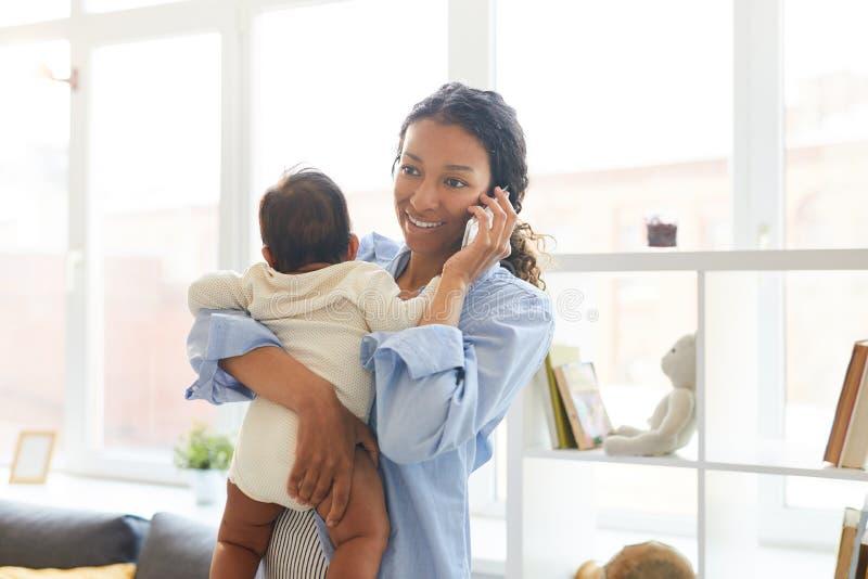 Madre joven que habla en el teléfono mientras que detiene al bebé fotografía de archivo
