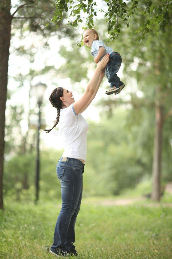 Madre joven que juega con el bebé en parque foto de archivo libre de regalías