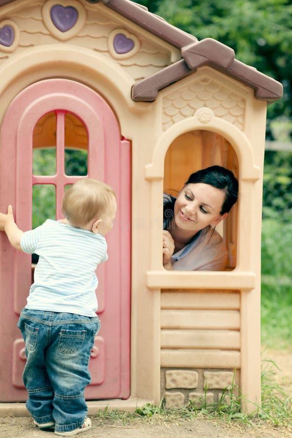 Madre joven que juega con el bebé en parque fotos de archivo libres de regalías