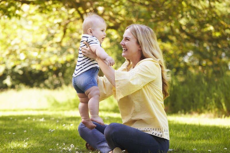 Madre joven que juega con el hijo del bebé al aire libre en jardín del verano imágenes de archivo libres de regalías
