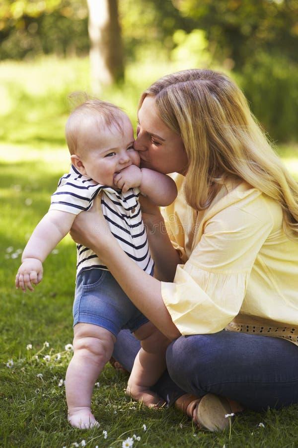 Madre joven que juega con el hijo del bebé al aire libre en jardín del verano imagen de archivo