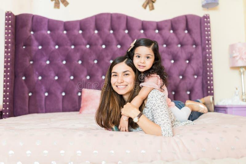 Madre joven que juega con la hija en cama foto de archivo