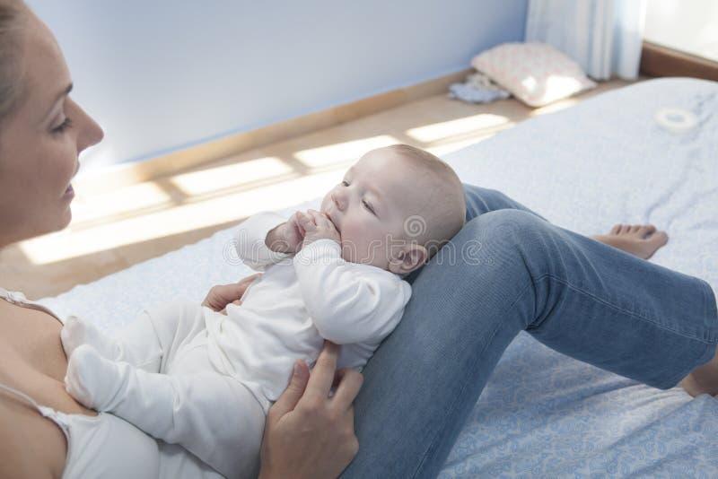 Madre joven que juega con su bebé después de alimentar el pecho fotografía de archivo