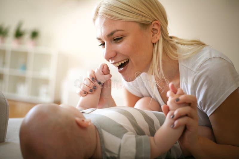 Madre joven que juega con su bebé en casa fotos de archivo