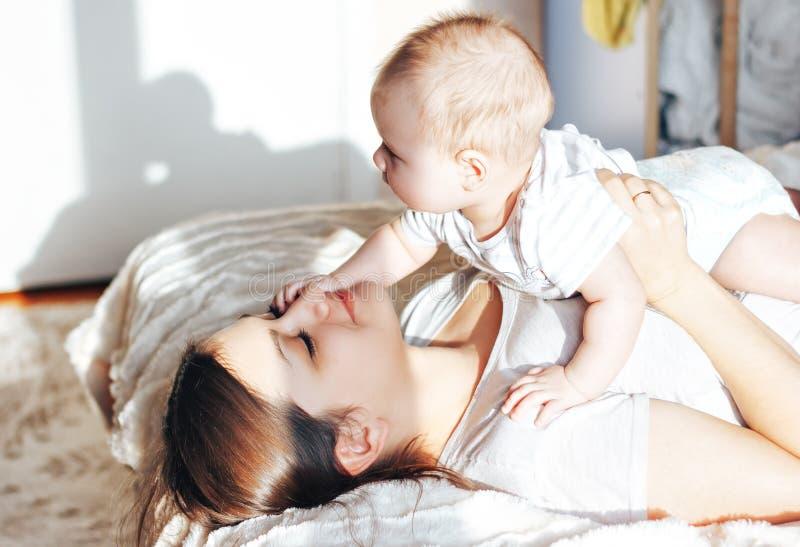 Madre joven que juega con su bebé en la cama, riendo imagenes de archivo