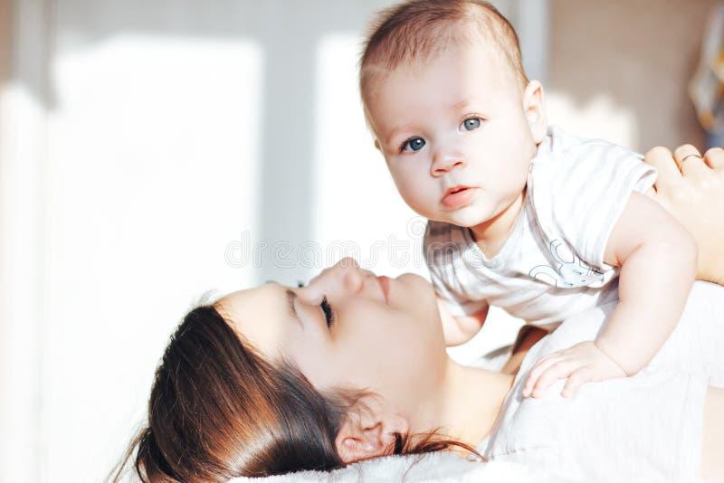 Madre joven que juega con su bebé en la cama, riendo foto de archivo