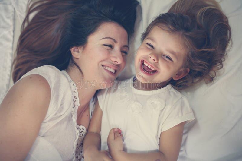 Madre joven que juega con su pequeña hija en cama Disfrute del toge imagenes de archivo