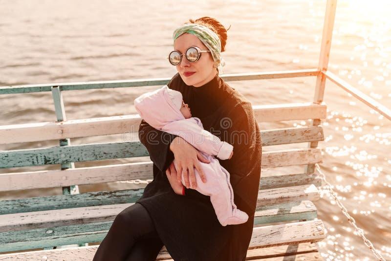 Madre joven que lleva a su hija adorable del bebé en un portador de bebé en parque hermoso del otoño detrás del lago imagenes de archivo