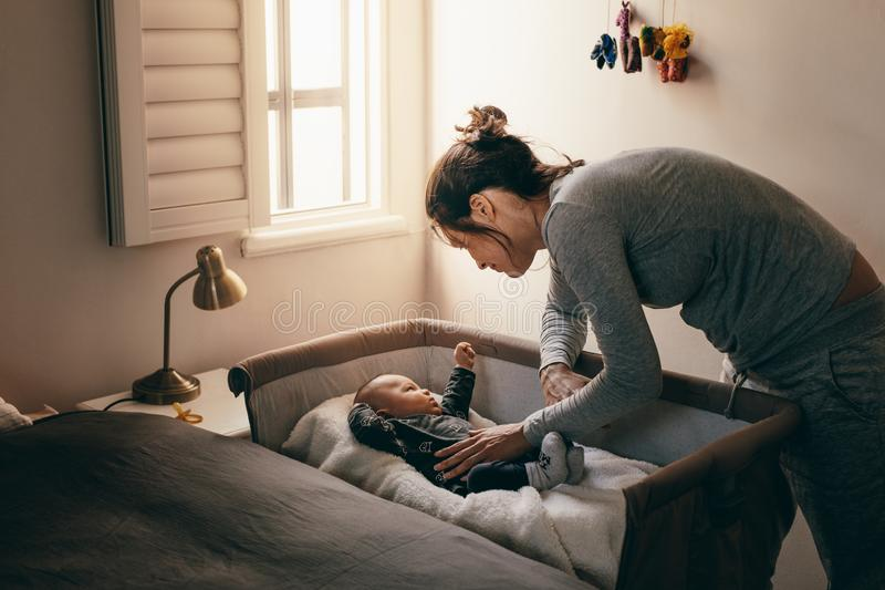 Madre joven que mira a su bebé que duerme en un pesebre imagenes de archivo
