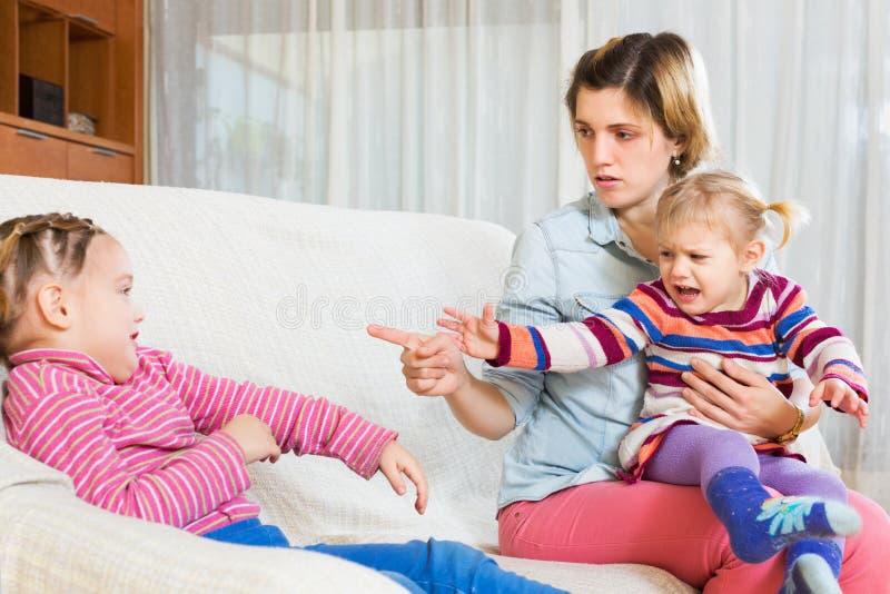 Madre joven que regaña a la pequeña hija fotos de archivo