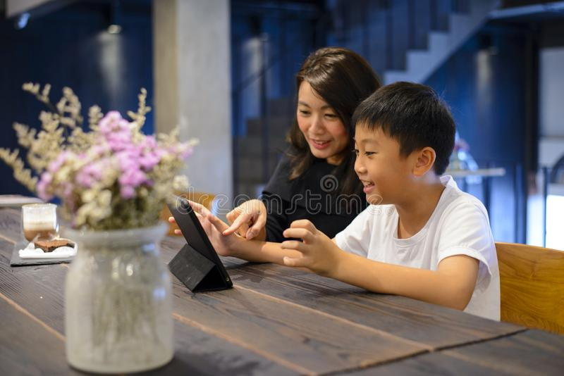 Madre joven que usa la tableta con su hijo en el café fotos de archivo libres de regalías