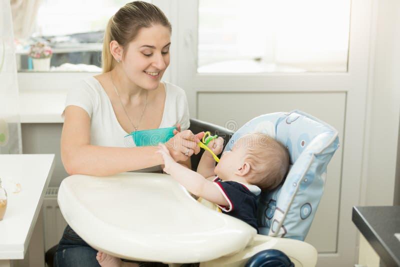 Madre joven sonriente que alimenta a su bebé en highchair fotografía de archivo