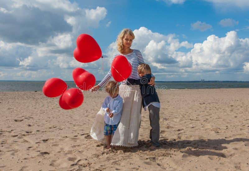 Madre joven y dos hijos que abrazan en la playa fotografía de archivo libre de regalías