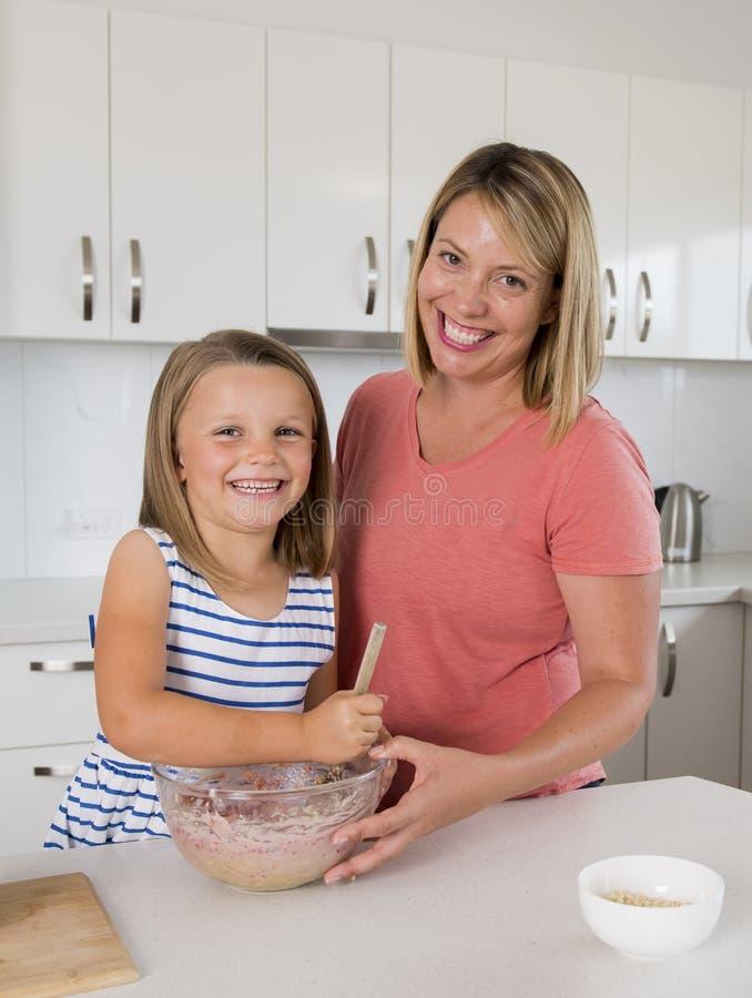 Madre joven y pequeña hija dulce que cuecen junto en casa la cocina feliz en concepto de la forma de vida de la familia fotos de archivo