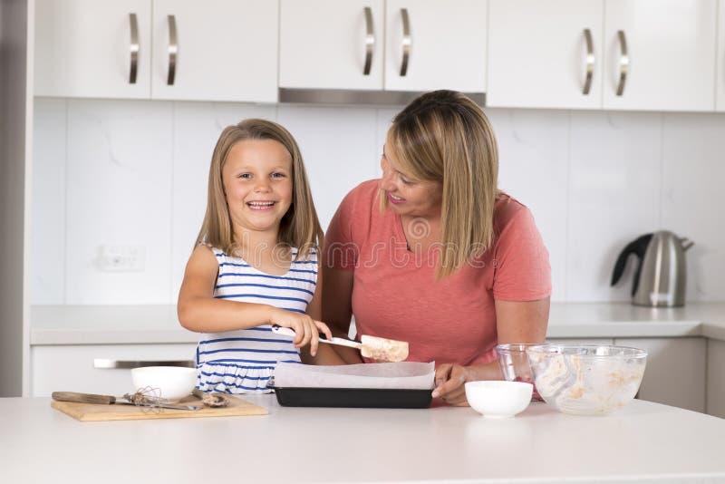 Madre joven y pequeña hija dulce que cuecen junto en casa la cocina feliz en concepto de la forma de vida de la familia imágenes de archivo libres de regalías