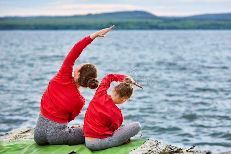 Madre joven y pequeña hija que hacen ejercicios de la yoga en el río cercano de piedra fotos de archivo