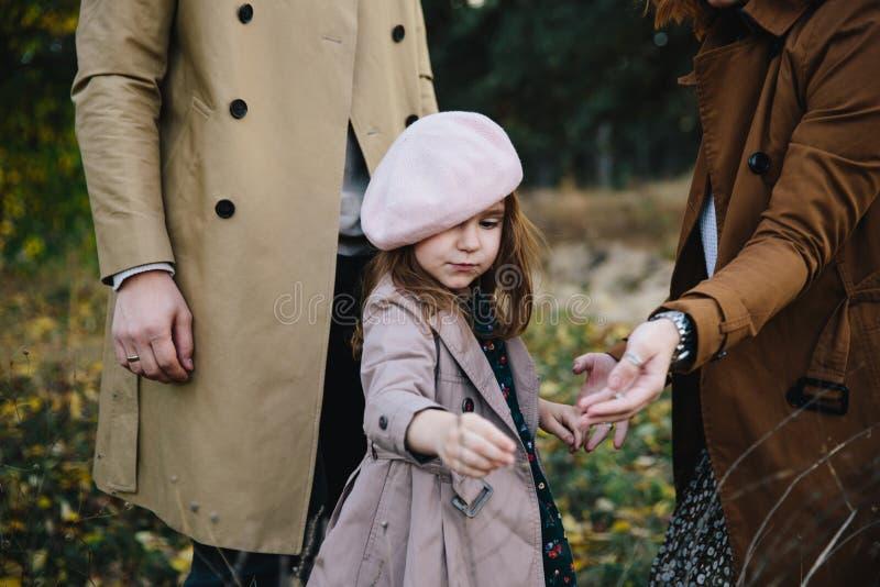 Madre joven y pequeña muchacha de la hija del niño en una boina y un paseo de la capa en el bosque del otoño foto de archivo libre de regalías