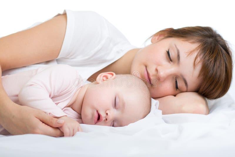 Madre joven y su bebé, durmiendo en cama imagen de archivo