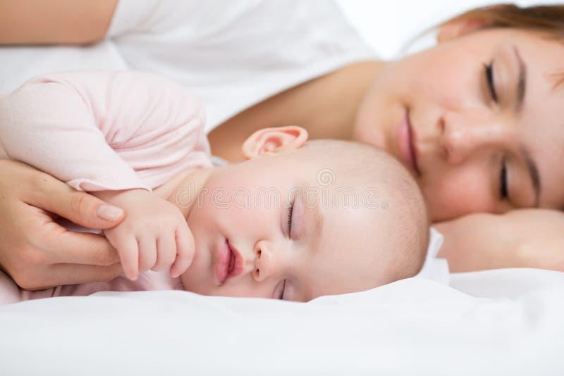 Madre joven y su bebé, durmiendo en cama fotografía de archivo