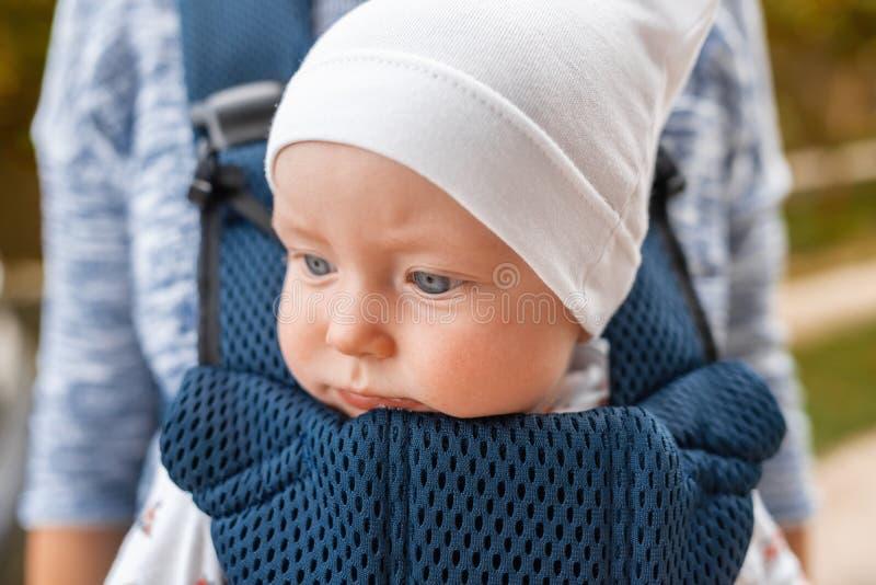 Madre joven y su beb? en un portador de beb? fotos de archivo libres de regalías