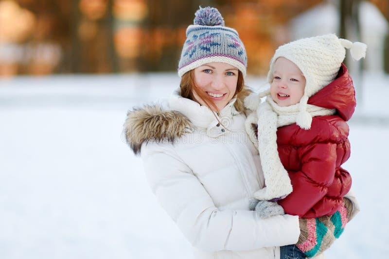 Madre joven y su hija del niño en el invierno fotografía de archivo