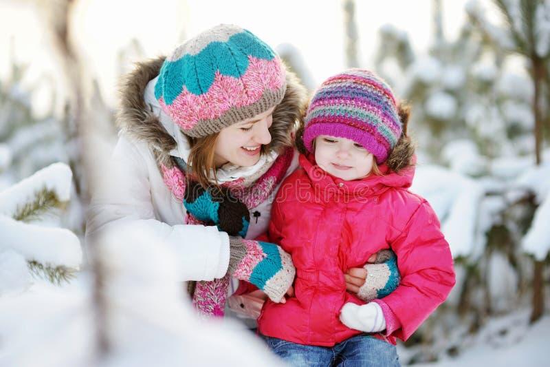 Madre joven y su hija en el invierno imagen de archivo