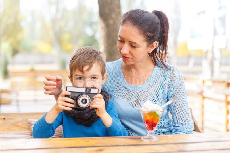 Madre joven y su hijo en un café El concepto de familia foto de archivo