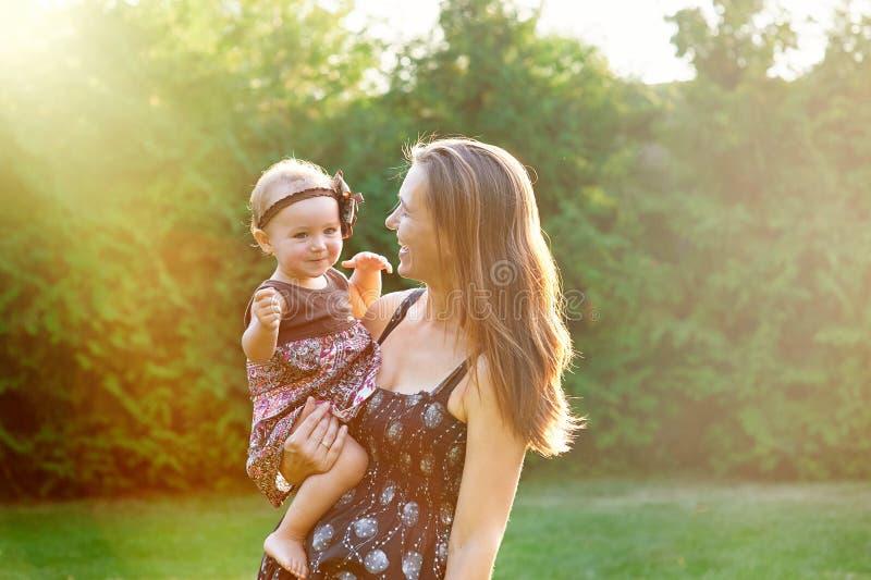 Madre joven y su pequeña hija que juegan en hierba fotos de archivo libres de regalías