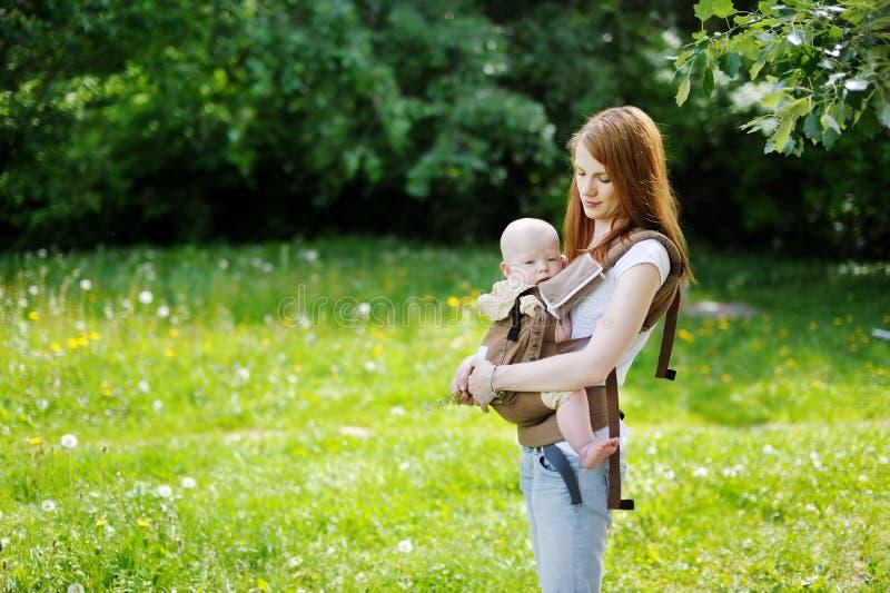 Madre joven y su pequeño bebé fotos de archivo