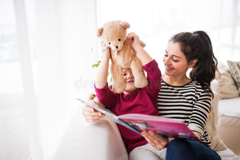 Madre joven y una pequeña muchacha con el oso de peluche en casa, leyendo un libro fotografía de archivo libre de regalías