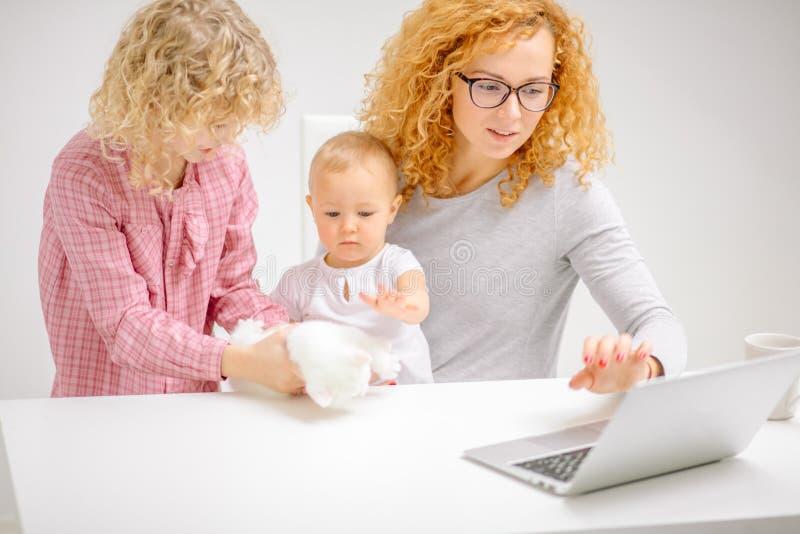 Madre laboriosa facendo uso del computer portatile mentre i suoi bambini che giocano con il gattino lanuginoso immagini stock libere da diritti