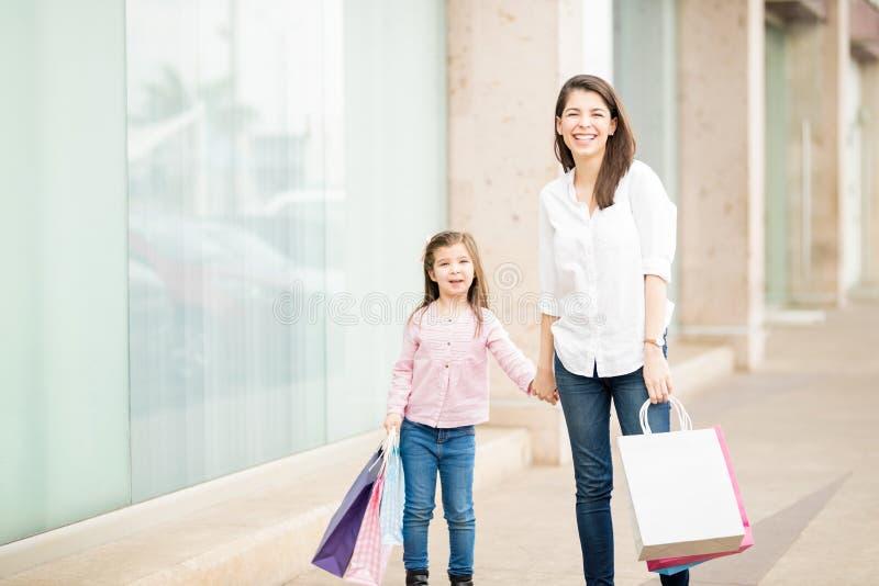 Madre linda e hija latinas que hacen un ciertas compras foto de archivo