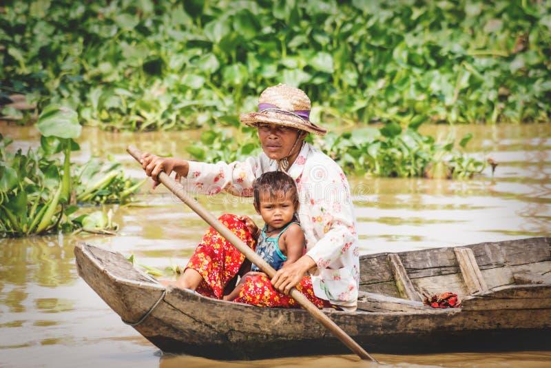 Madre locale cambogiana con un bambino che cammina lungo il lago Tonle Sap, Puok, provincia di Siem Reap, Cambogia immagini stock